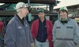 BCIT women in trades; welding, students talking while standing around inside a welding shop [2 of...