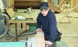 Male First Nations student wearing safety goggles and maneuvering a piece of wood [1 of 5 photogr...