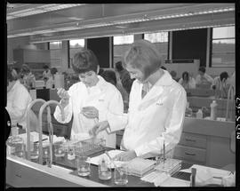 Medical laboratory technology, 1967; two students in lab coats using lab equipment ; students wor...