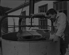 Tire repair, Nanaimo, 1967; a student using a machine to pour water on a tire a large metal basin