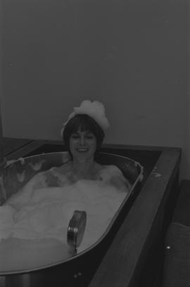 Woman sitting in a bubble filled metal tank with bubbles on her head