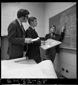 BCIT Business Management image of two students with an instructor teaching standing at a blackboa...
