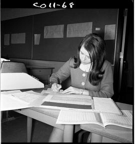 B.C. Vocational School; Commercial Program student in a classroom working at a desk with an addin...