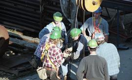 Ironwork, students wearing tool belts, hard hats and uniforms while using the tip a crane (?) [6 ...