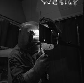 Welding, Terrace, 1968; man wearing protective goggles and gloves welding small pieces of metal [...