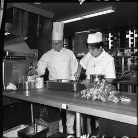 BC Vocational School Cook Training Course ; student stirring food in a pan on a counter ; instruc...