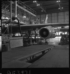 BC Vocational School; Aeronautics instructor and students working on the wing of a jet airliner C...