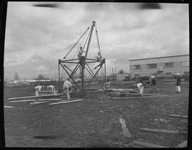 Structural steel, 1968; students constructing a steel structure in a field