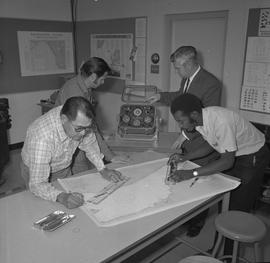 Navigation, 1968; two men measuring a nautical chart ; two men using navigational compasses [2 of 2]