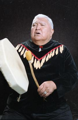 Bob George, First Nations elder, in First Nations garment playing an instrument [30 of 36 photogr...