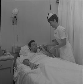 Nursing, 1968; a nurse attending to a patient checking respiration