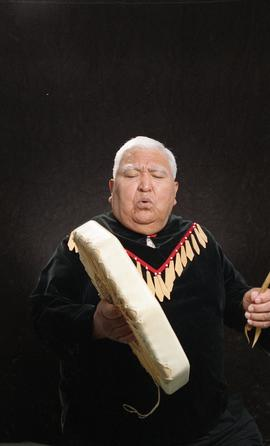 Bob George, First Nations elder, in First Nations garment playing an instrument [9 of 36 photogra...