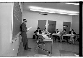 BCIT Business Management image of an instructor leaning against a blackboard speaking to students...