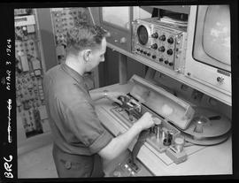 Man working at tape reel station [1 of 2 photographs]