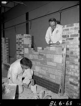 B.C. Vocational School image of a Bricklaying student building with bricks with an instructor che...