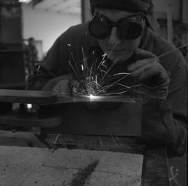 Welding, Terrace, 1968; person wearing protective goggles and gloves welding