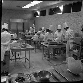 BC Vocational School Baking Course ; instructor demonstrating to two students ; students working ...