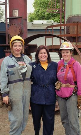 Steel trades; Anne St. Eloi in between two other women wearing hard hats, uniform and safety gear...