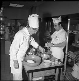 BC Vocational School Cook Training Course ; student preparing food while the instructor tests the...