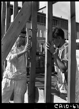 B.C. Vocational School image of two Carpentry Trades students using a level to check the straight...