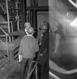 Forestry, Wood fiber BCIT tour, November 26, 1965; men wearing hard hats standing in a factory