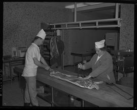 Meat cutting, 1968;  two people cutting pork ; man in background carrying part of a pig on his sh...