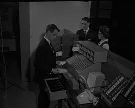 Hotel Motel, 1966; man in a suit processing a receipt at a staged hotel reception desk, two peopl...