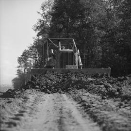 Logging, 1969; a man driving a Caterpillar dozer to move dirt [2 of 2]