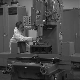 Mechanical technology, 1968; man in a lab coat adjusting a drill bit on a drill