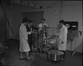 Food Processing Technology, 1966; instructor demonstrating to three students in lab coats how to ...