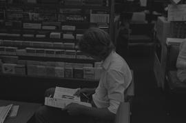 Man sitting down and reading a newspaper; magazine rack in background