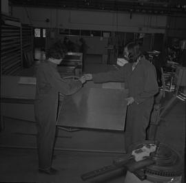 Sheet metal, 1968; two students holding a piece of sheet metal working next to a piece of machine...