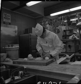 BC Vocational School Cook Training Course ; a student chopping onion
