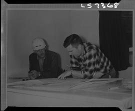 Logging, 1968; copy negative; picture of two men sitting at a desk looking at maps