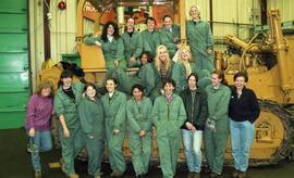 BCIT women in trades; heavy duty, students in uniforms standing in front of a bulldozer [7 of 9 p...