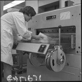 BCVS Graphic arts ; person adding paper to a paper cutting machine