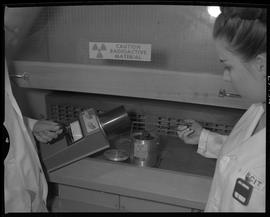 Medical isotope option, Health technology, 1967; female picking up radioactive material with tong...