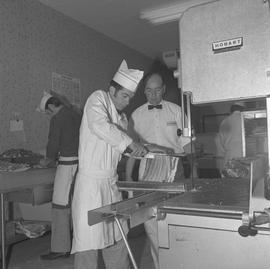 Meat cutting, 1968;  a student cutting ribs and the instructor watching ; students working in bac...