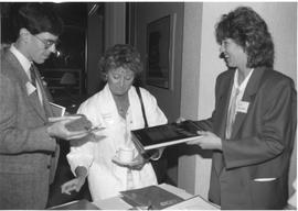 Alumni Association, 1987; Allison Dewhurst (right) showing a book to two people