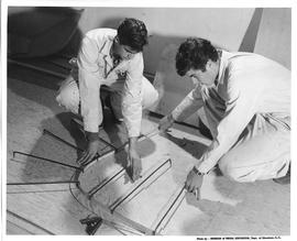 Two men kneeling down and measuring wood for boat building; Photo by the Division of Visual Educa...