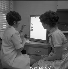BC Vocational School Dental Assistant program ; two students examining x-rays of teeth [2 of 2]