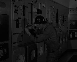 Instrumentation, 1964; man wearing a hard hat fixing a piece of instrumentation equipment [2 of 2]