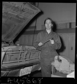 B.C. Vocational School image of an Automotive Mechanics program woman student holding a wrench an...