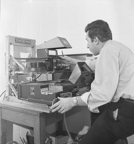 BCVS Graphic arts ; a man adjusting the settings on a photo typositor