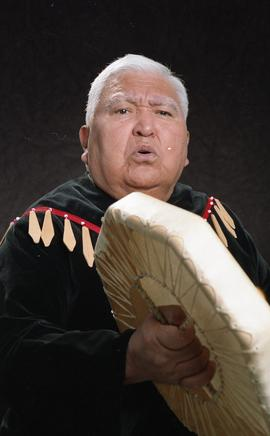 Bob George, First Nations elder, in First Nations garment playing an instrument [18 of 36 photogr...