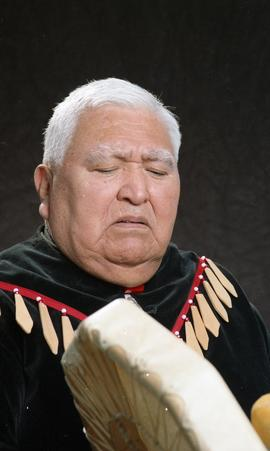 Bob George, First Nations elder, in First Nations garment playing an instrument [1 of 36 photogra...