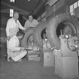 Tire repair, Nanaimo, 1967; instructor watching two students checking the air pressure of a tire ...