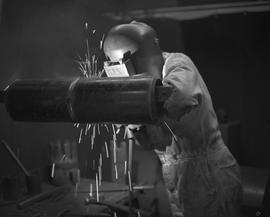 Welding, 1968; a person wearing protective gear welding