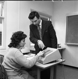 BC Vocational School Commercial Program; instructor talking to a student using a comptometer