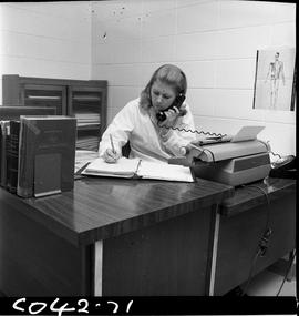 BC Vocational School Commercial Program; woman at office desk recording information while speakin...